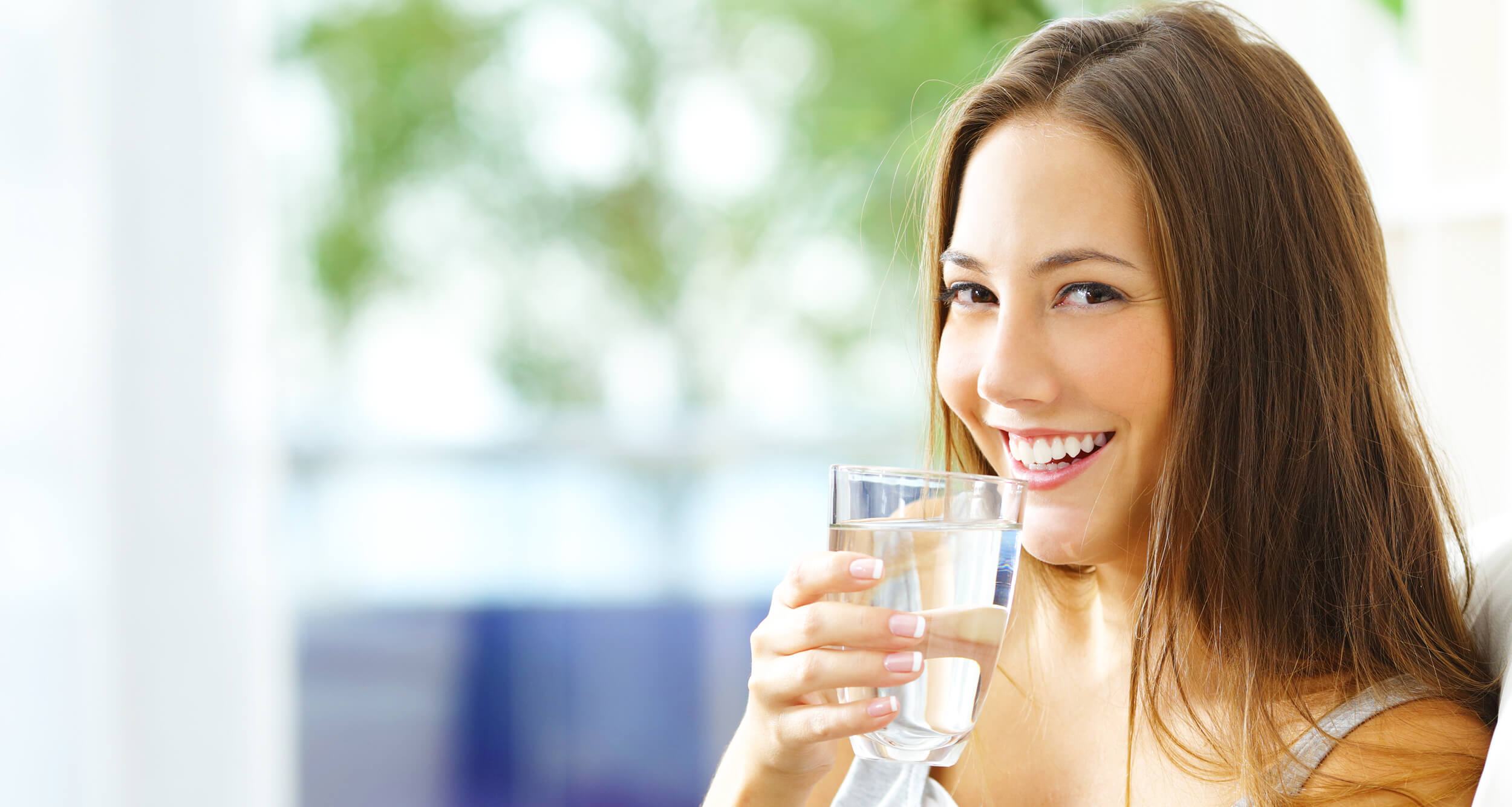 A Girl Showing Her Teeth While Smiling and Holding Glass of Water
